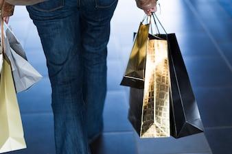 Woman walking with shiny shopping bags