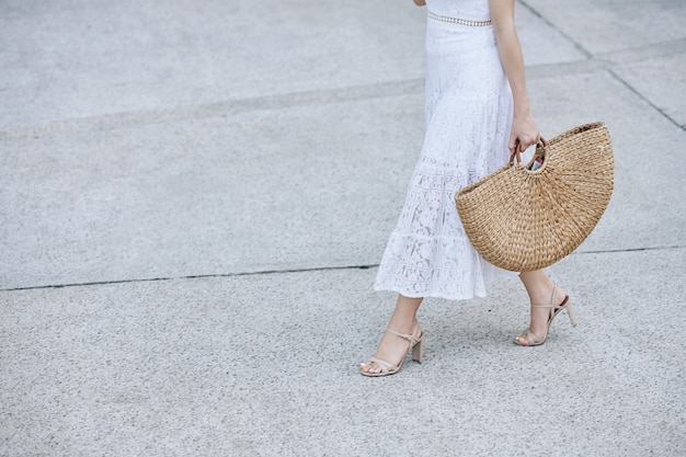 Woman walking with straw bag