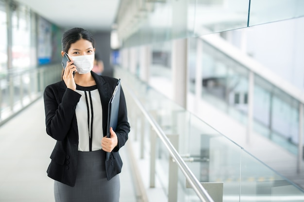 Woman walking with surgical mask face protection walking and calling for business looking away in crowds at airport train station work commute to hospital.