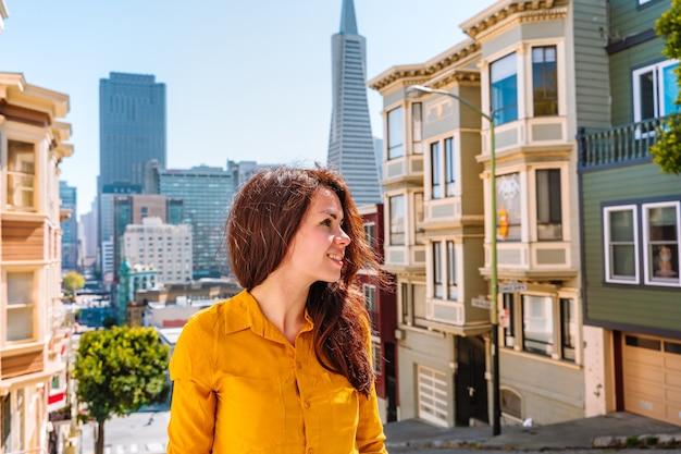 샌프란시스코의 transamerica tower가 보이는 아름다운 거리를 따라 걷는 여성