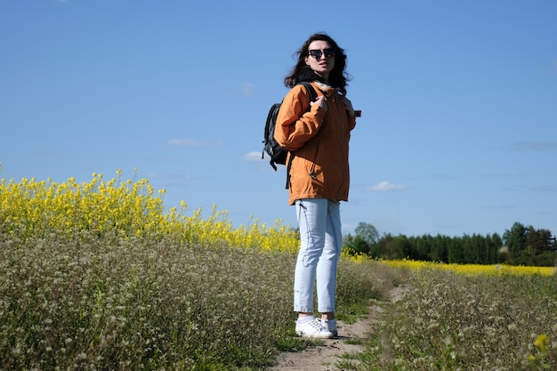 Woman walks along a rural road along a meadow with flowers