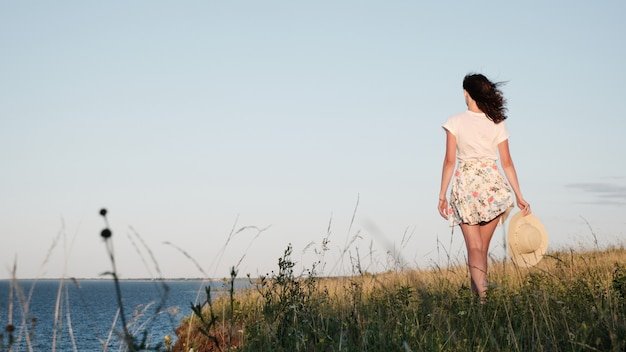 A woman walks along the shore and holds a hat in her hand.