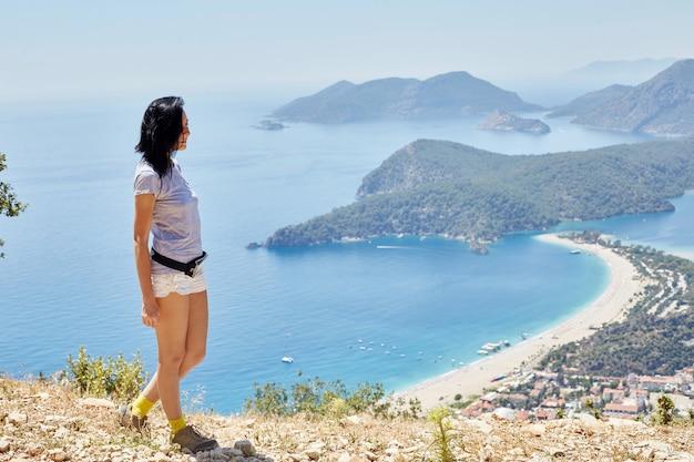 女性はリシアンウェイトレイルに沿って歩きます。フェティエ、オルデニズ。海とビーチの美しい景色。トルコの山でのハイキング