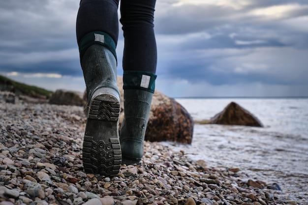 女性は湖の岩の多い岸に沿って歩きます。雨の空。夜遅く。街の外を旅する