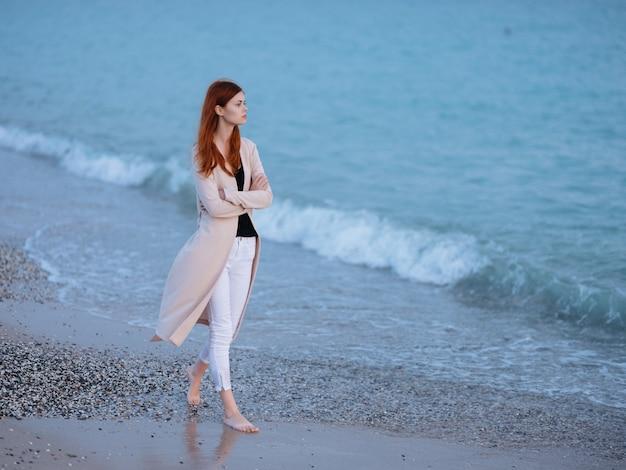女性は海岸の海の風景の休暇の夜のロマンスに沿って歩きます