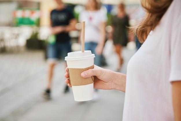 Женщина идет по улице города с бумажной кофейной чашкой