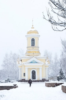 A woman walks to the christian chapel under the snow in the city in blizzard.