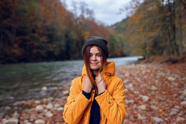 여자는 노란색 재킷 산 여행에 가을 숲에서 산책. 고품질 사진