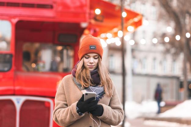여자는 겨울 거리를 걷고 스마트 폰에 메시지를 씁니다.