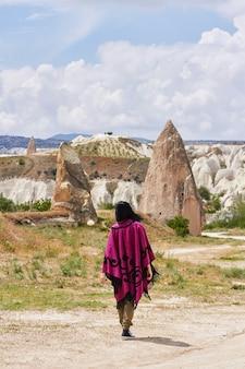 Woman walks in between mountains in cappadocia turkey