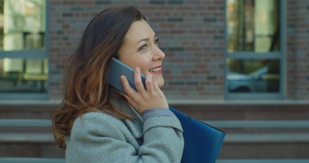 Женщина ходит возле бизнес-центра с документами и разговаривает на смартфоне.