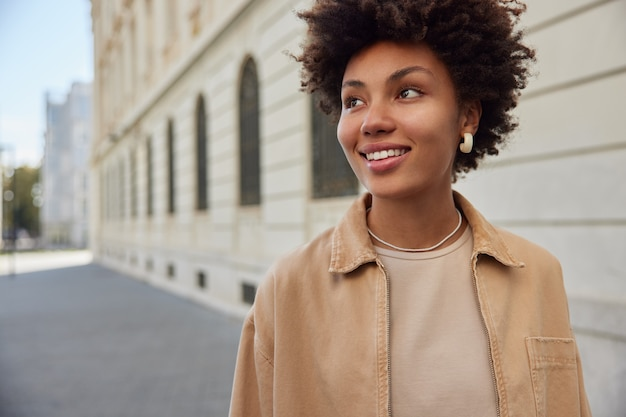 Donna cammina all'aperto passeggia in una piccola bella città intorno a edifici antichi sorride felicemente indossa abiti eleganti gode del tempo libero in vacanza ha un'espressione felice