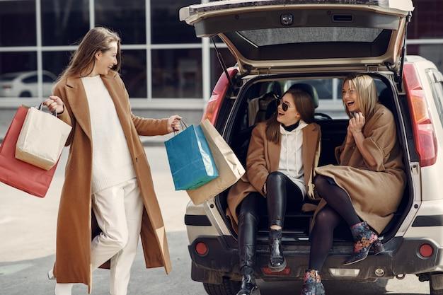 女性は買い物袋で外を歩く