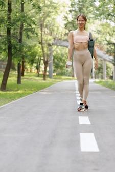 女性はトレーニングのためにスポーツウェアで公園を歩きます
