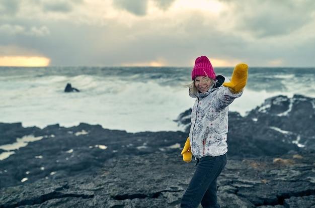女性は曇りの天気で黒い火山砂のある海岸で、見事な海の景色を楽しみながら歩きます。
