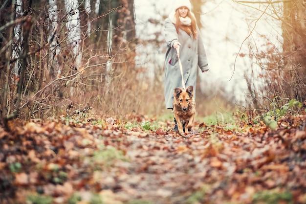 女性は森の中で犬と一緒に歩きます。