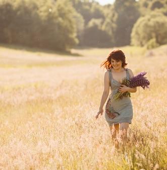 Woman walks with bouquet of lavander across the field