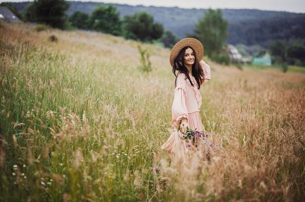 Woman walks with bouquet of lavander across green field