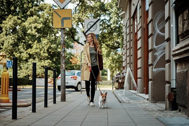 女性は犬と一緒に歩く
