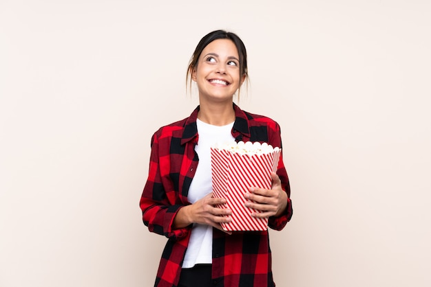 Woman over wall holding a big bucket of popcorns