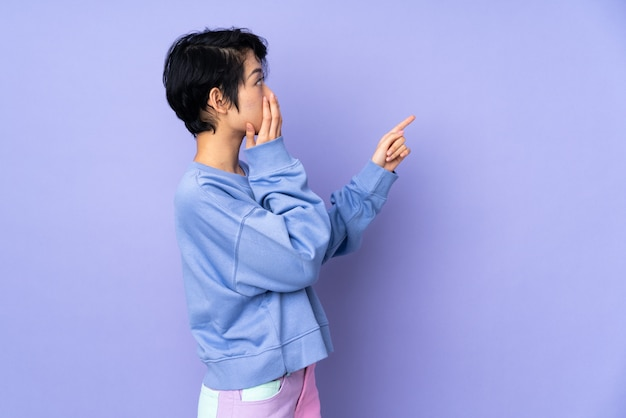 Woman over wall pointing at one side with surprised expression