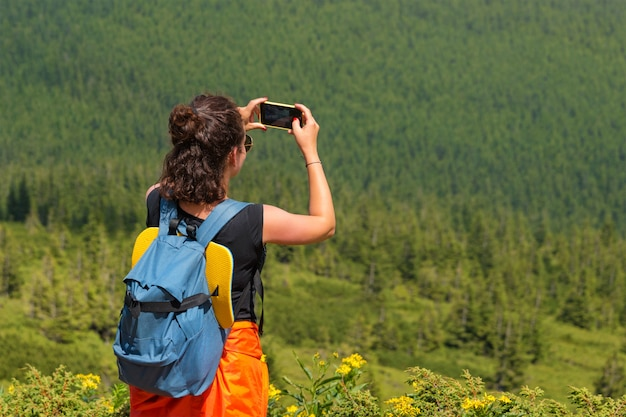 Женщина страсть к путешествиям фотографируя ландшафт природы пейзажа на smartphone в лесе. молодая самка, принимая фото на сотовые. фотограф природы турист снимает стоя на вершине горы.
