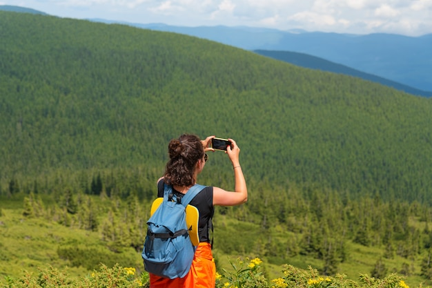 Woman wanderlust photographing scenery nature landscape on smartphone in the mountains.