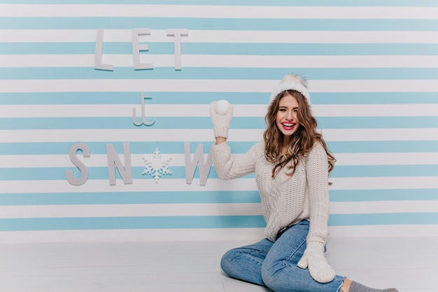 Woman wanting to play snowballs. full-length female portrait indoors against striped wall