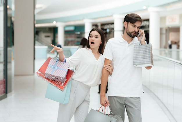 Woman wants to go to store but man is busy talking on phone.