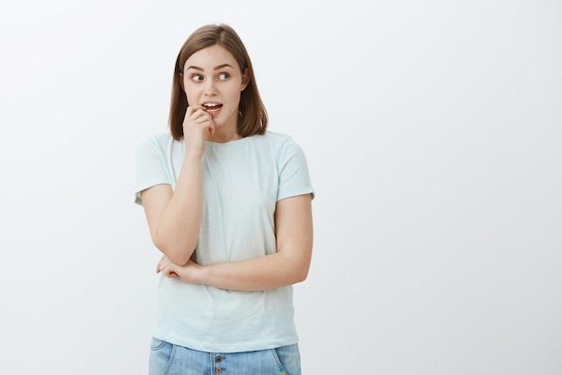 女性はダイエットが許せば躊躇してお菓子をつかむことを望んでいます。欲望で見つめていると思いながら爪を噛んで興味深く興味津々の興奮して集中しているかわいい女性
