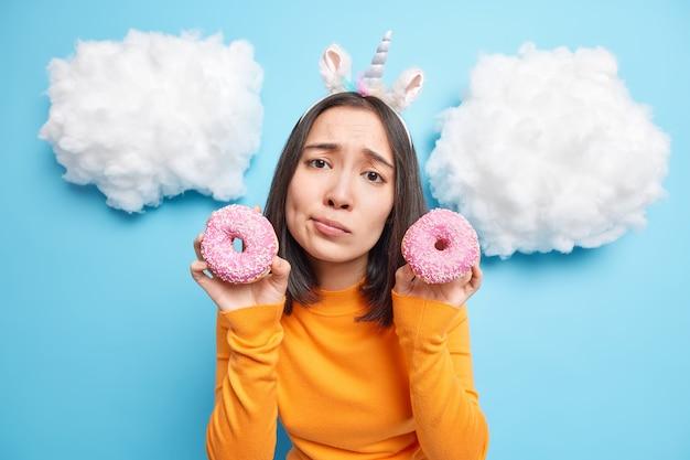 女性は甘いおいしいスナックを食べたいと思っています 2 つの艶をかけられたドーナツを持ち、菓子を楽しむ青に分離されたオレンジ色のジャンパーを着ています