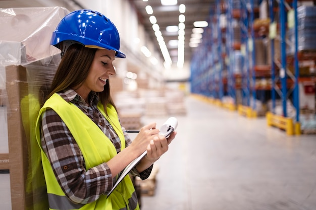 Woman warehouse worker leaning on cardboard boxes and taking notes in large warehouse distribution center