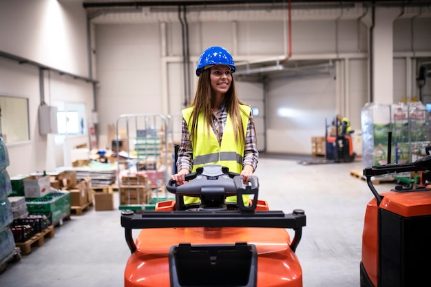 Woman warehouse worker with hardhat and reflective safety equipment driving forklift machine in large distribution warehouse center