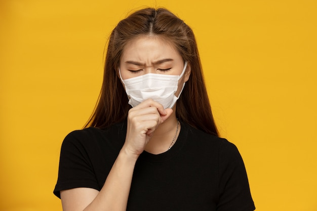 Woman waring protection mask from coronavirus and air pollution coughing so sickness isolated