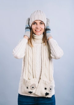 Woman in warm clothes covering ears