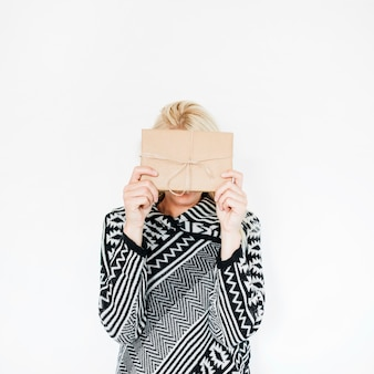 Woman in warm clothes hiding face behind present