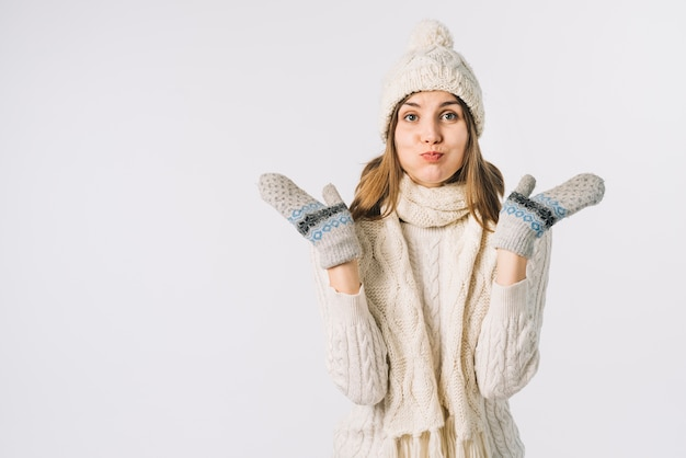 Woman in warm clothes puffing cheeks