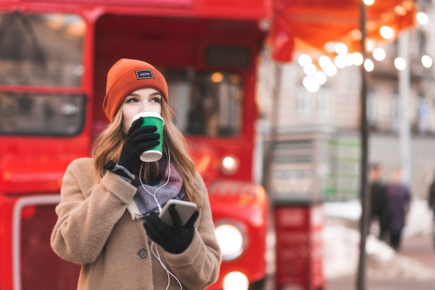 Woman in warm clothes, standing on the background of a red bus with a smartphone in her hands, drinking coffee from a green cup and looking sideways