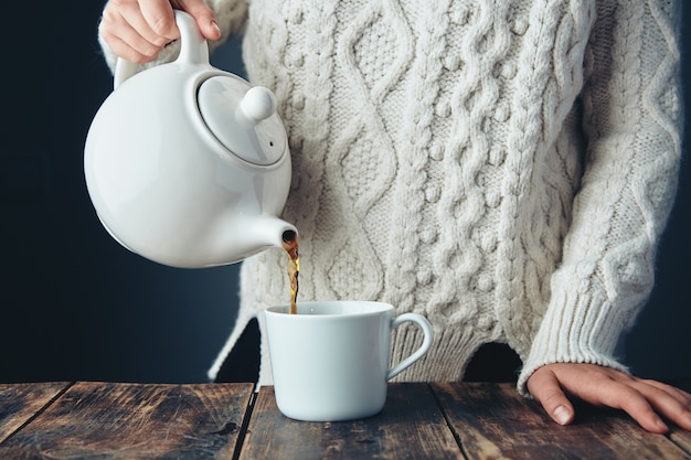 Woman in warm knitted thick sweater pours black tea from big white teapot to cup on grunge wooden table. front view, anfas, no face.
