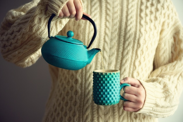 Woman in warm knitted woolen sweater holds turquoise teapot and pouring herbal tea into handmade cup. copy space. winter and christmas holidays concept
