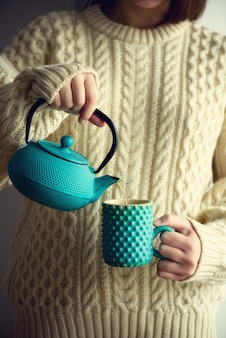 Woman in warm knitted woolen sweater holds turquoise teapot and pouring herbal tea into handmade cup. copy space. winter and christmas holidays concept.