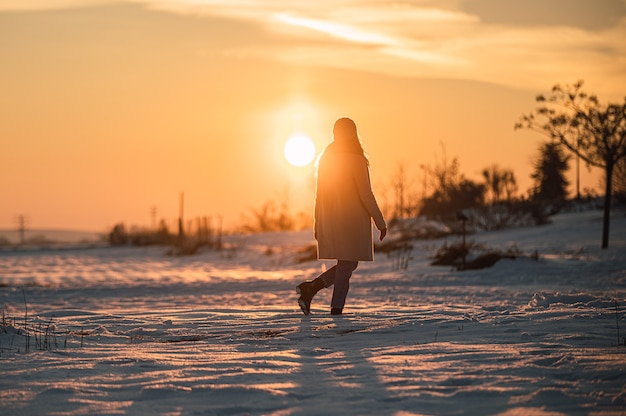 Woman in warm outfit standing alone among snowy meadow and admiring picturesque sunset in winter countryside