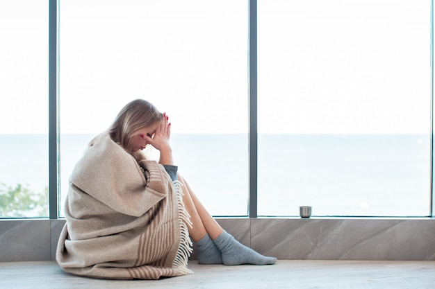 Woman in warm socks sitting on a floor near large window wrapped in a blanket, holding her head, having a strong headache.