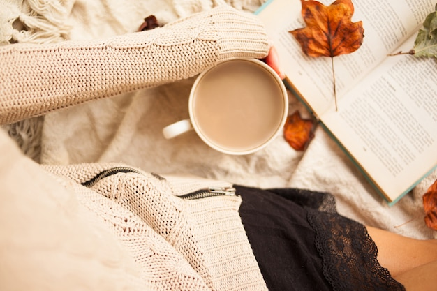 Woman in warm sweater and checkered plaid with cup of coffee latte in hands sitting with book
