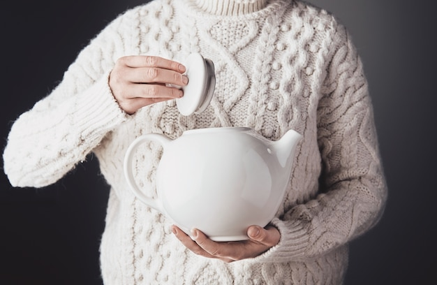 La donna in maglione caldo tiene una grande teiera di ceramica bianca da un lato e apre il cappuccio con l'altro