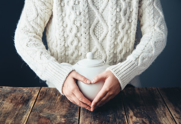 Woman in warm sweater holds hands on big white teapot with tea in heart shape. front view, grunge wooden table. anfas, no face.