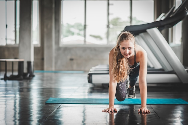 Woman warm up before workout in fitness gym