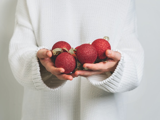 Woman in warm white sweater holding christmas red balls in hands