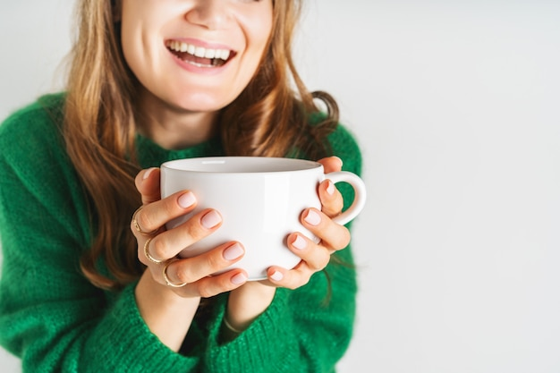 Woman in warm wool green sweater is holding white mug in her hands with coffee or tea. mock up for winter mood design. minimal style.