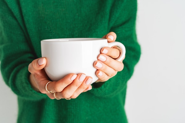 Woman in warm wool green sweater is holding white mug in her hands with tea. mock up for winter mood design. minimal style.